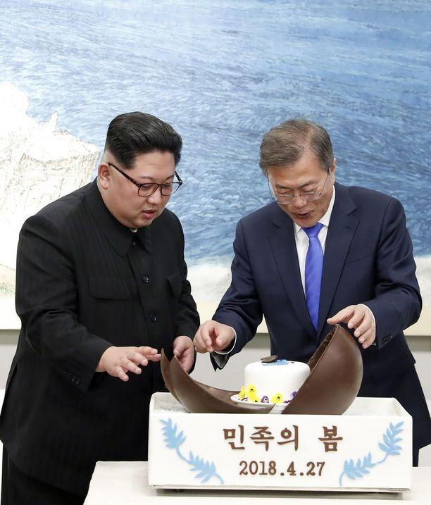 Etelä-Korean presidentti Moon Jae-in (oik.) ja Pohjois-Korean johtaja Kim Jong-un puuhastelivat harvinaisessa tapaamisessaan yhdessä muun muassa suklaakuoreen piilotetun kakun parissa.