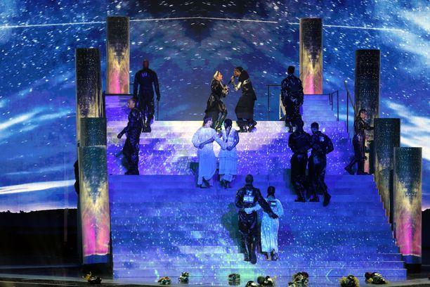 Viimeisinä portaita nousevilla tanssijoilla on Israelin ja Palestiinan liput selkämyksissään.