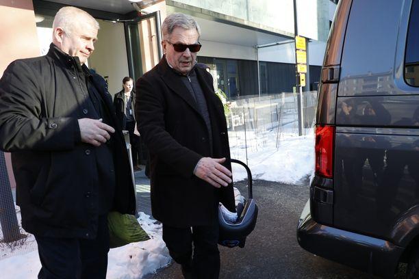Presidentti Sauli Niinistö kantaa kuopustaan turvakaukalossa.