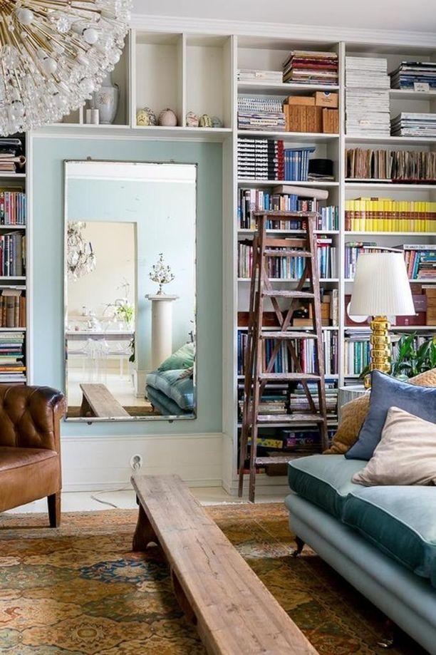 Peili keskellä avartaa seinätilaa, joka muuten on peitetty kirjahyllyllä.