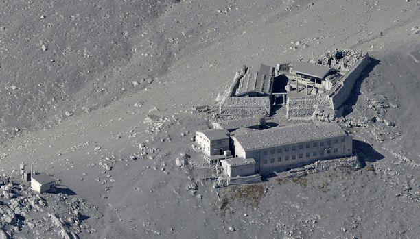 Tuhkan peittämiä rakennuksia lähellä tulivuoren huipun kraatteria.
