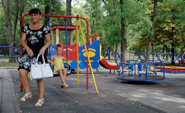 Larissa viettää tyttärensä Kristinan kanssa kuumaa aamupäivää Mariupolin ainoassa suuressa lasten leikkipuistossa.