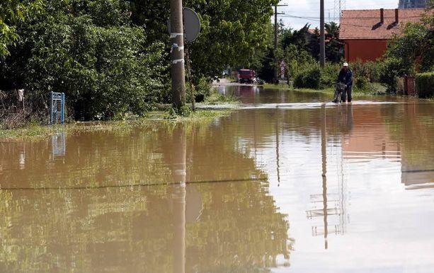 Mies työnsi polkupyöräänsä tulvavedessä Veliki Crljenin kylässä Serbiassa, noin 30 kilometrin päässä Belgradista.