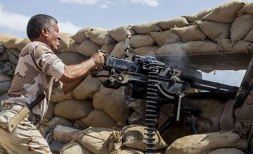 Kurdien peshmerga-sotilas tulittaa Isisin asemia Irakin puolella. Kuva on vuodelta 2015.