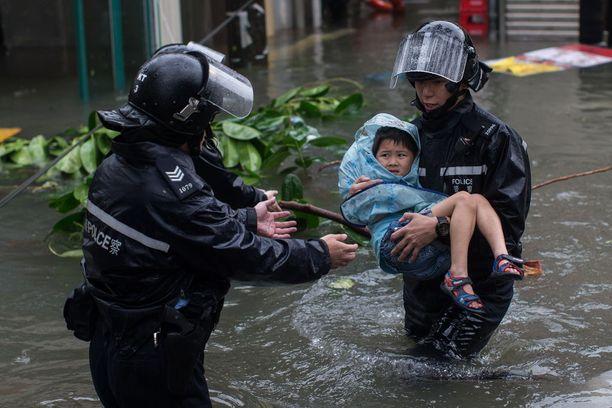 Poliisit pelastivat lasta tulvavesien keskeltä Hongkongissa sunnuntaina.