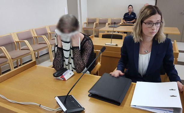 Nainen peitti kasvonsa oikeudessa.