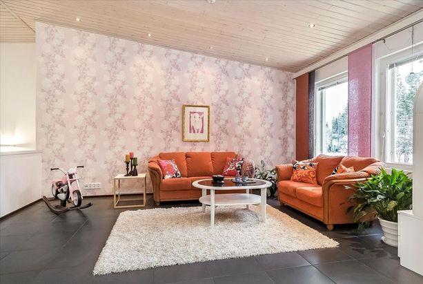 Olohuoneessa on yhdistelty rohkeasti vaaleanpunaista ja oranssia.