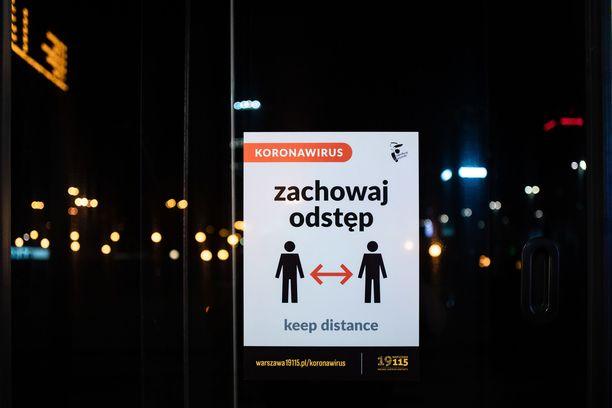 Varsovassa ihmisiä opastetaan julistein pitämään sopivaa turvaetäisyyttä toisiinsa.