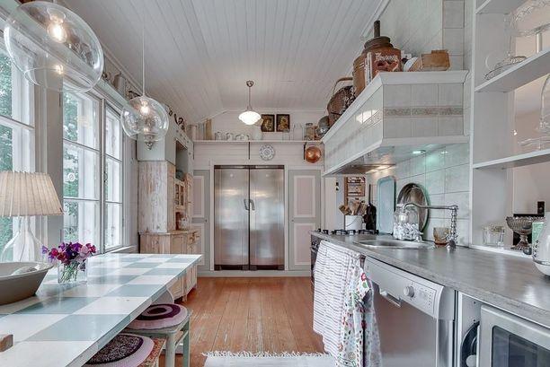 Keittiöstä näkyy, miten uudenaikaiset laitteet ja esineet voivat sointua kauniisti maalaisromanttiseen tyyliin. Keittiön seinistä löytyy myös helmipaneeli.