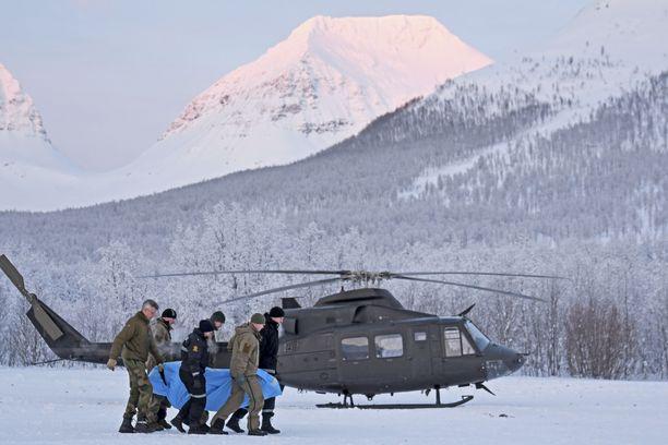 Poliisin ja Punaisen Ristin edustajat kantoivat helikopteriin Tamokdalenista torstaina löytynyttä uhria.