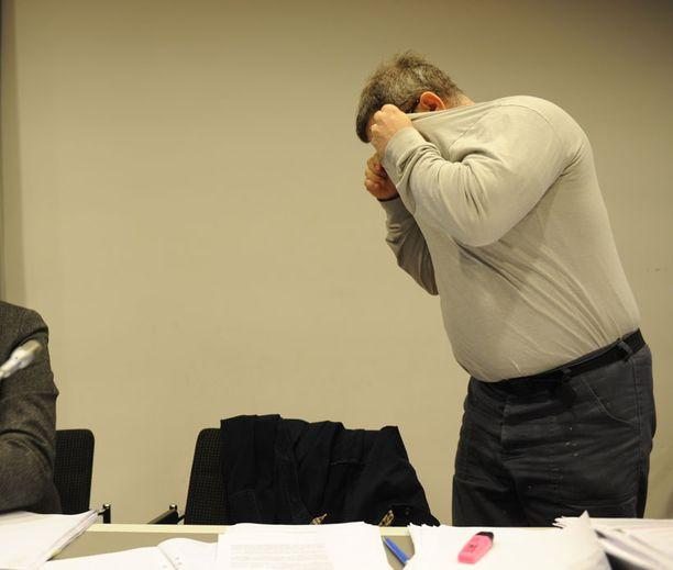 Juha Louhi (ent. Turunen) peitteli kasvojaan kuvaajilta oikeudessa joulukuussa.