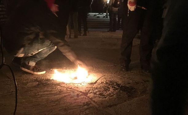 Jotkut soihtukulkueen osallistujista sammuttivat soihtunsa hautausmaan kivijalkaan.