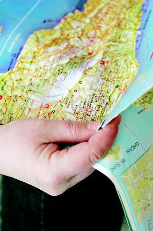 Koko perhe tutkii matkakohteiden karttoja huolella etukäteen.