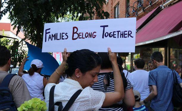 """""""Perheet kuuluvat yhteen"""" julistaa mielenosoittajan kantama kyltti New Yorkissa kesäkuun lopulla. Yhdysvaltojen hallinnon kovat toimet siirtolaisia kohtaan ovat herättäneet runsaasti keskustelua Yhdysvalloissa."""
