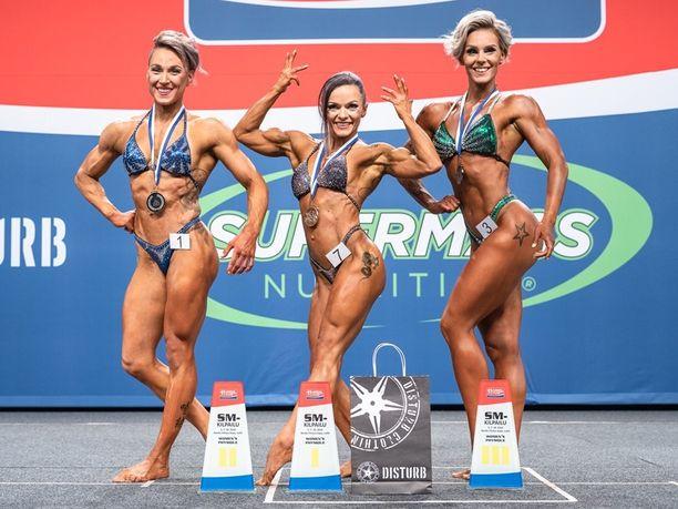 Tanja Ekola (kesk.) voitti amatöörien SM-kultaa naisten fysiikkakisoissa lokakuussa Lahdessa. Vieressä toiseksi tullut Hanna Soininen ja kisan kolmas Ulpu Silvennoinen. Sarjassa kilpaili kaikkiaan seitsemän naista.