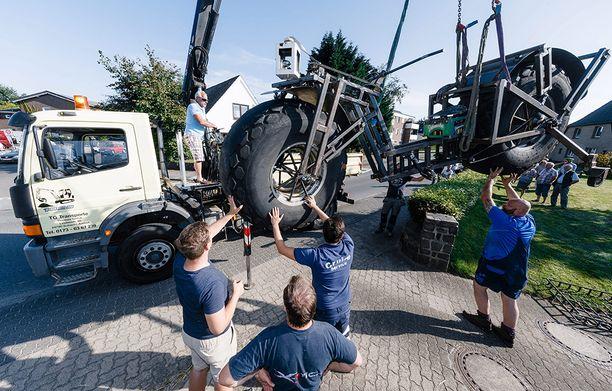Naapurit auttavat Frank Dosea saamaan ennätyspyörän kuorma-auton kyytiin.