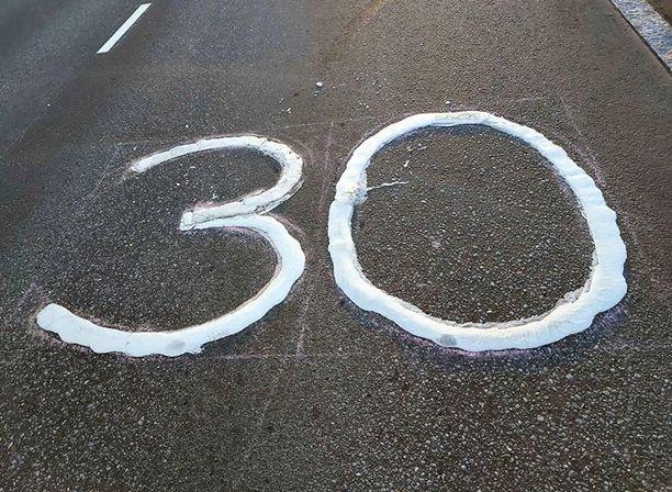 Tämä tiemerkintä kertoo 30 kilometrin tuntivauhdin nopeusrajoituksesta Kummunkadulla.