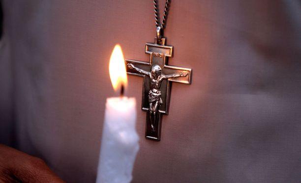 Pakistanilainen pitää kynttilää kädessään Lahoressa talebanien tekemän terrori-iskun uhrien muiston kunniaksi.