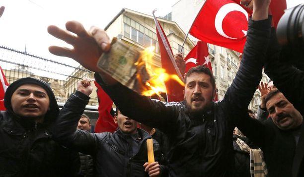 Vihaiset Erdoganin kannattajat osoittivat mieltään Hollannin lähetystön edessä Istanbulissa viikonloppuna. Kuvassa palava seteli on USA:n dollari.