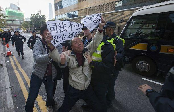 """Poliiseja vastaan mieltään osoittanut mies Hongkongissa tiistaina ennen oikeudenkäyntiä, jossa poliisit todettiin syyllisiksi. Kyltissä lukee """"yhteiskunnan epäoikeudenmukaisuus vapauttaa radikaaleja""""."""