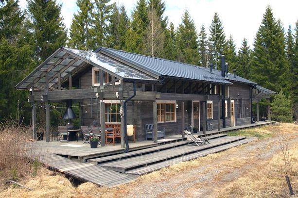 Talo on vuodelta 2012, mutta harmaa hirsiverhoilu luo mielikuvan vanhasta, maisemaan istuvasta rakennuksesta.