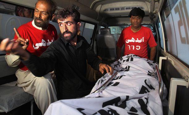 Keskellä Kashmiri Abdul Majeed veljensä Shafqat Hussainin ruumiin vieressä.