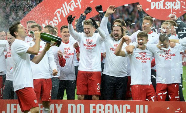 Puolan pelaajat joivat samppanjaa kentällä EM-kisapaikan varmistuttua.