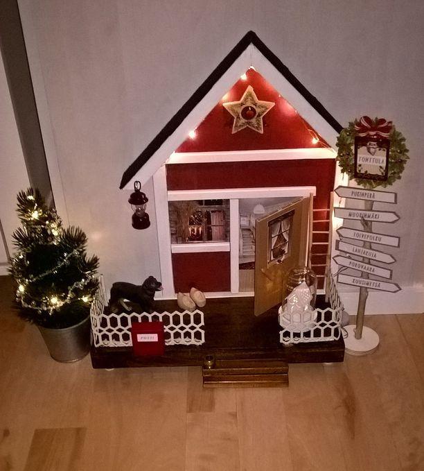 -Meidän tonttuovi on tehty kovalevyn pohjalle ylijäämätavaroista. Katolla on oikeaa kattohuopaa, kaiteet suihkun pesuainetelineestä. Tämähän on rintamamiestalon kuistin pääty, ja ovesta näkyvät portaat yläkertaan, Mikko kertoo. Oveen ja ikkunaan on liimattu kuvat joulukorteista.