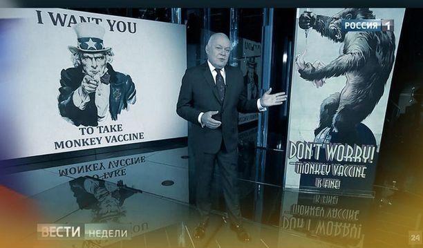 """Ajankohtaisohjelman juontajan takana olevassa kuvassa King King sanoo """"Älä huolehti, apinarokote on ihan hyvä""""."""