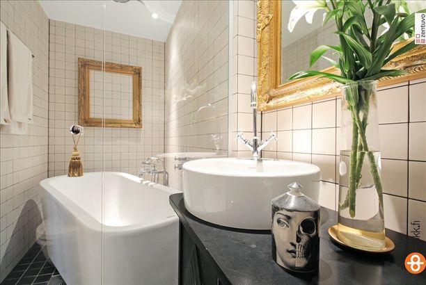 Eipä uskoisi, että kyseinen kylpyhuone on yksiöstä! Kultaiset sisustusesineet tuovat ripauksen luksusta, jykevät kalusteet laaduntuntua ja vanhanaikaiset kaakelit tunnelmaa.