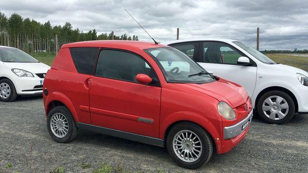 Mopoauto (punainen) ei juuri liikenteessä poikkea ulkonäöltään pineimmistä henkilöautoista. Rakenteissa ero on suuri.