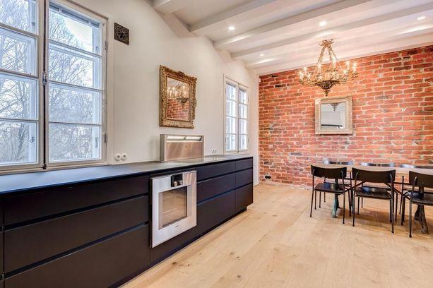 Ensimmäisen kerroksen salimaisen osan jatkeena on tiiliseinäinen keittiö.