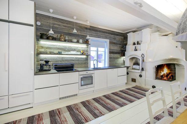 Keittiössä yhdistyvät monet vaikutteet. Valkoinen moderni keittiö ei pilaa vanhaa tunnelmaa hirsineen ja leivinuunineen - päinvastoin: tunnelma on raikas.