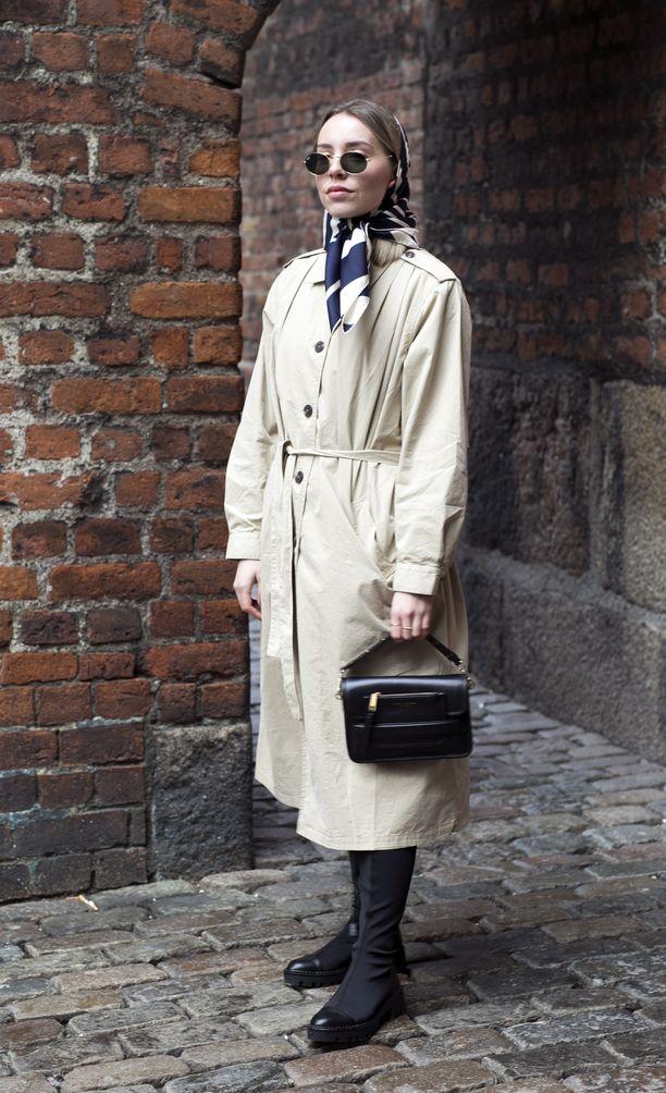 Vintage-henkisten huivin, trenssin sekä laukun liitto henkii menneitä vuosikymmeniä. Tyyli viimeistellään 60's-henkisillä pohjemittaisilla saappailla.