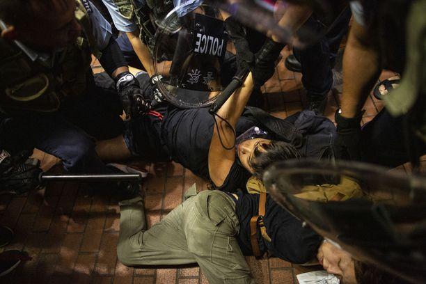 Mellakkapoliisit pitävät lakimuutosta vastustavaa mielenosoittajaa maassa Hongkongissa.