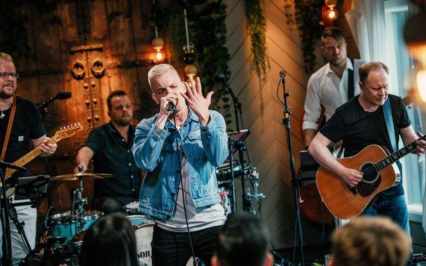 Elastinen esittelee sormustaan vasemmassa kädessä, kun mies esittää Lauri Tähkän Morsian-kappaleen Vain elämää -ohjelmassa.