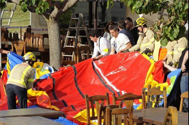 Palomiehet raivasivat Caldes de Malavellassa onnettomuuspaikkaa, jossa pomppulinna lähti yhtäkkiä lentoon tuhoisin seurauksin.