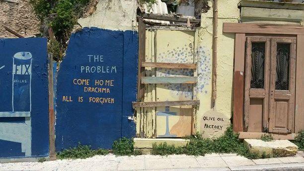 Kansanäänestys näkyy kaduilla. Plakassa ränsistynyttä seinää koristi graffiti, joka toivotti entisen valuutan drakman tervetulleeksi kotiin.