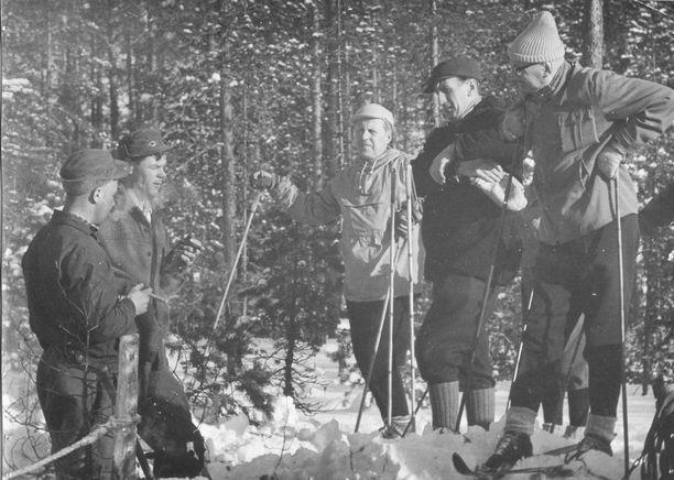 Presidentti keskustelemassa metsätyömiesten kanssa.