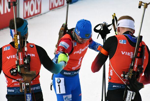 Aleksandr Loginov ojensi kätensä MM-takaa-ajon jälkeen kultamitalisti Émilien Jacquelille (vas.). Oikealla Norjan Johannes Bö.