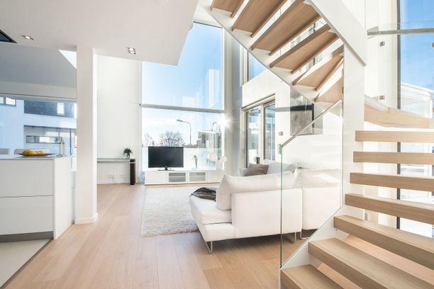 Tämän kodin yläkerrokseen nousee tyylikkäät portaat avaran olohuoneen luota.