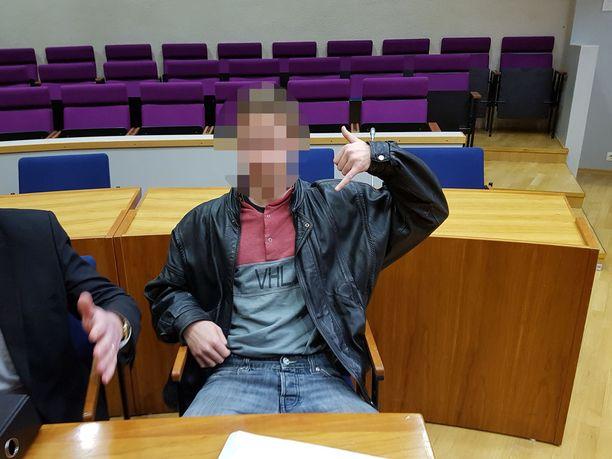 """Hyväntuulinen tutkintavanki näyttää """"soitellaan""""-merkkiä kuvaajalle oikeussalissa. 17-vuotias lastenkodista karkuteillä ollut puukotti mustasukkaisuusdraamassa samanikäistä kaveriaan ja seuraavana iltana uudelleen samaa kaveria ja myös omaa isäänsä, joka oli tulossa ottamaan kiinni poikaansa, kun oli kuullut edellisen illan puukotuksesta."""