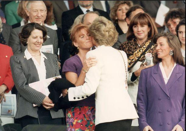 Diana tervehti poskisuudelmalla Sarahia Wimbledonin tennisottelussa vuonna 1990.