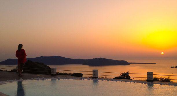 Auringonlaskun ihailija uima-altaan partaalla.