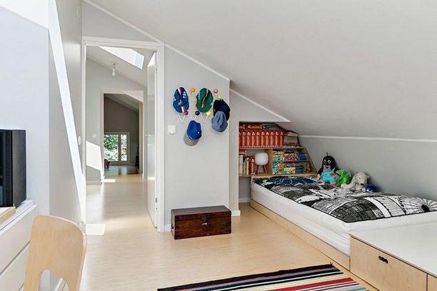 Tässä suloisessa huoneessa kaltevan katon alle lapsella on oma luku- ja unipesä. Pienessä kirjahyllyssä voi säilyttää suosikkikirjoja.