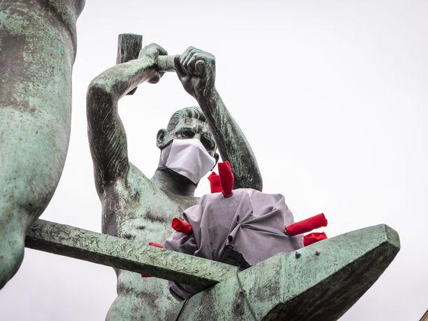 Kolme seppää takovat koronavirusta maskit kasvoillaan Helsingissä.