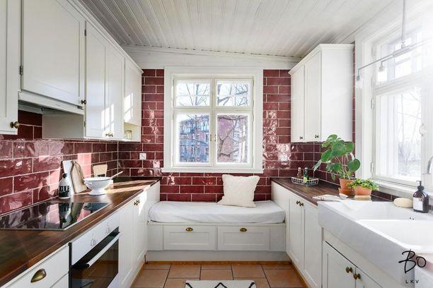 Keittiö saa rustiikin ilmeensä punertavista käsintehdyistä laatoista, puisista tasoista, messinkisistä vetimistä ja laattalattiasta.