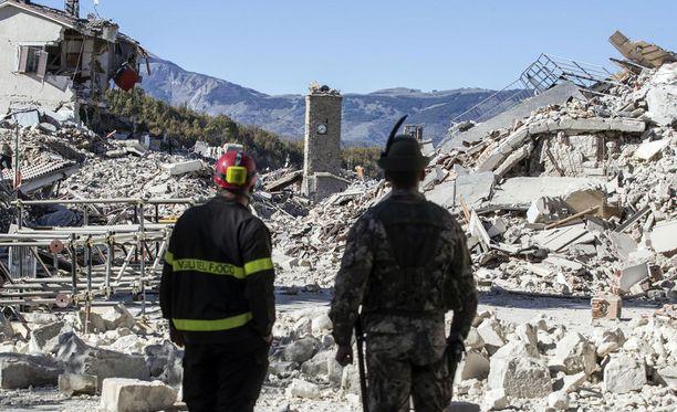 Pelastustyöntekijät katsastavat tuhoja Amatricen keskustassa.