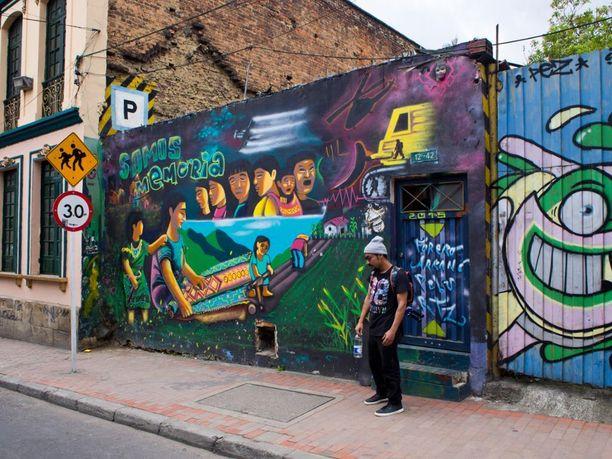 Graffiti, joka kuvastaa Kolumbian lähimenneisyyttä. Oikealla näkyy espanjalaiselle Pezille tyypillinen naurava hahmo. Keskellä Bogotan graffitikierroksen vetäjä Rey Garcia.