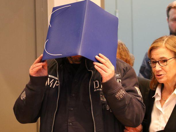Högel suojasi kasvojaan saapuesaan oikeussaliin. Tapausta seuraa noin 80 toimittajaa.